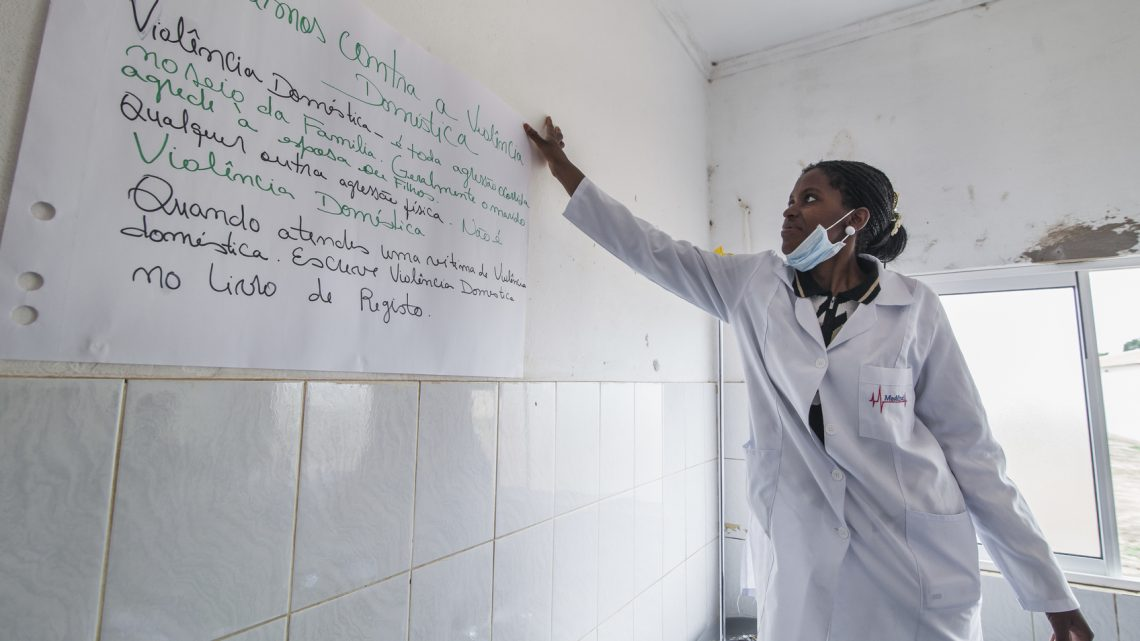 Bie, Angola - October 23, 2013: A midwife puts a poster in the wall of a public hospital about early detection and support to victims of gender based violence.