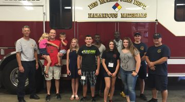 A small group of youth rally attendees visit with firefighters after delivering a care package and thanking them for their service.