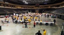 Staff volunteers, including those representing ACSDR in bright gold shirts, guide evacuee role players through the various stations of assistance during the National Mass Care Exercise held in Kansas City in August.