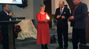 Pastor Jose LaPorte, treasurer Linda White and elders David White and Ira Thompson participate in a mortgage burning ceremony at the Rolla Church