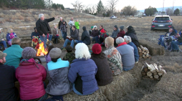 Bernie Hartnell, building committee chair, points out the location of the church, school and childcare facilities during a New Year's Eve campfire on the new property. Photo: Ron Carrick