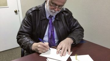 Pastor Ted Williams signs baptismal certificates for three men at Crowley County Correctional Facility in Olney Springs, Colorado. Photo: Rajmund Dabrowski