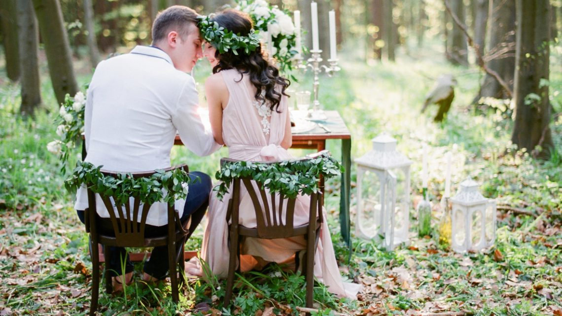 Groom and bride sitting at the table setted for two
