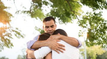 Latin father and daughters embracing in circle