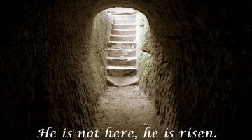 An empty tomb leading to a brightly lit staircase