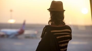 Woman looking at planes, back view