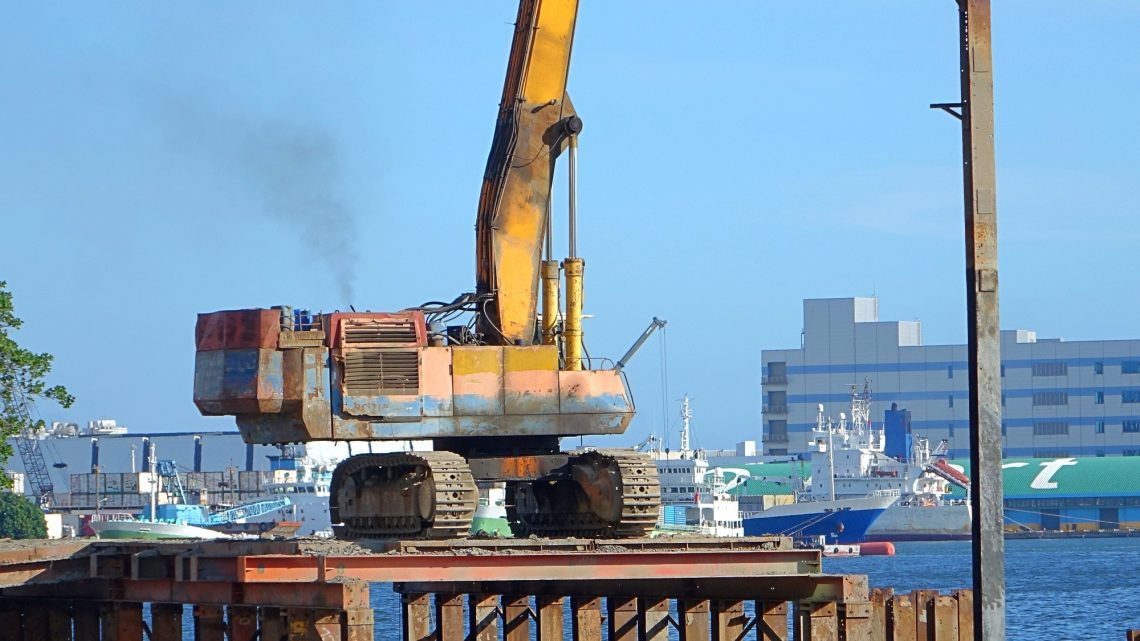 A hydraulic pile driver sinks a large support post into the river bed for bridge construction.