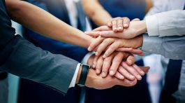Closeup shot of a group of businesspeople joining their hands together in unity