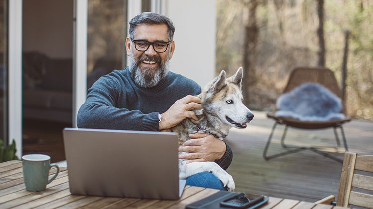 man at computer with dog